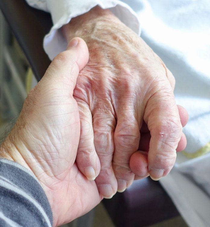 eine ältere Hand liegt in einer jüngeren