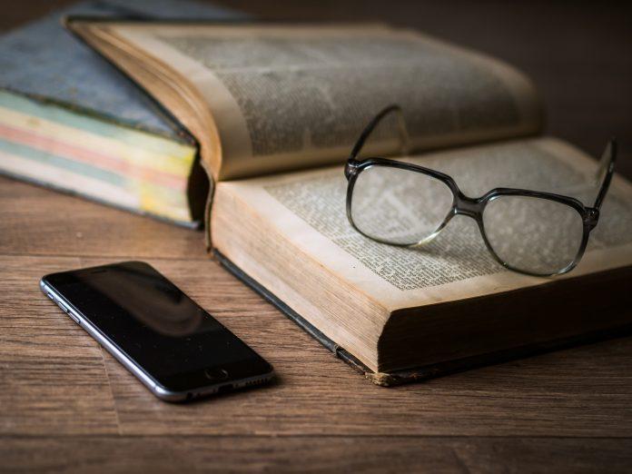 Ein aufgeklapptes Buch, eine Brille und ein Mobiltelefon liegen auf einem Tisch