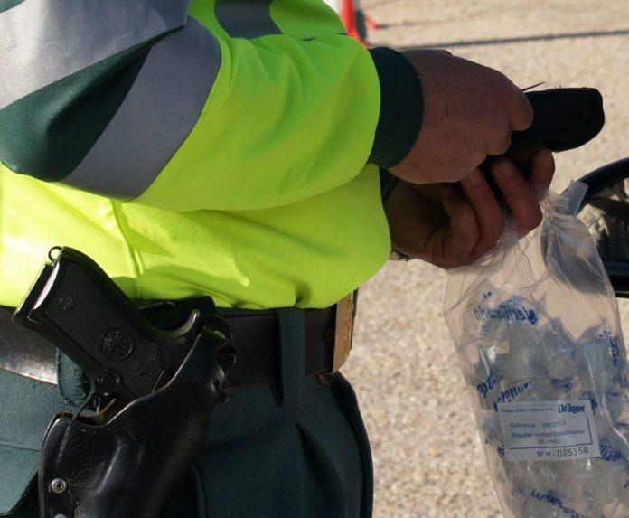 Polizist mit Atemalkohol-Messgerät an einem Auto