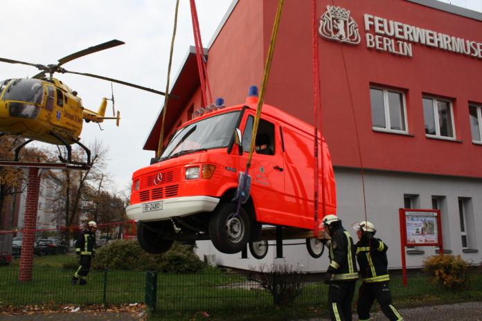 Der halbe Rettungswagen hängt vor dem Feuerwehrmuseum am Kran und soll an seinen Platz kommen
