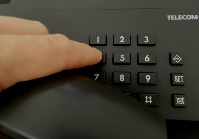 Hand wählt auf Telefon-Tastatur
