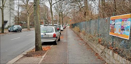 Radweg entlang einer Straße mit geparkten Autos