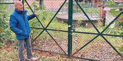 Mann vor einem Zaun