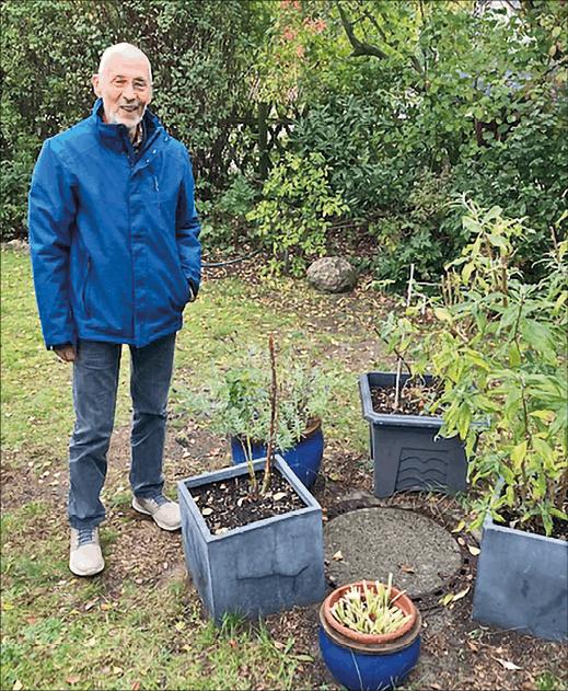 Mann im Garten mit Blumentöfpfen um einen Gullydeckel