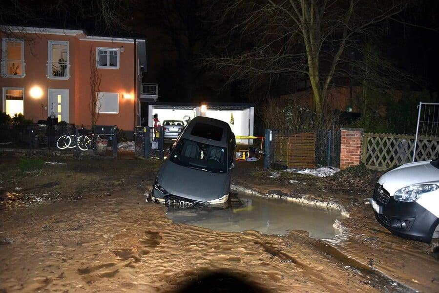 Auto steckt mit der Front in Straßenkrater