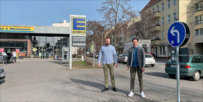 zwei Männer auf einem Supermarktparkplatz