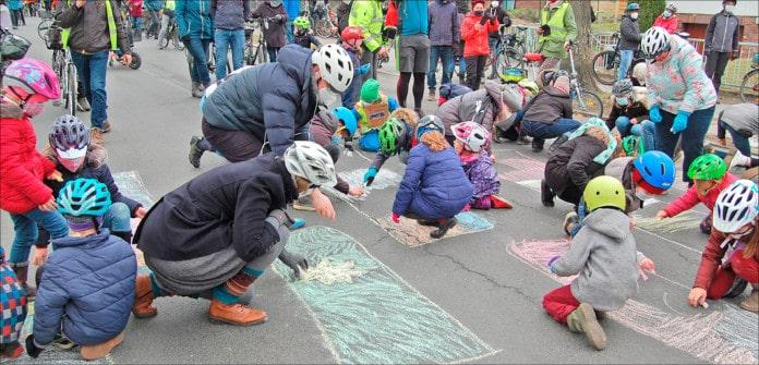 Kinder malen mit Kreide auf einer Straße