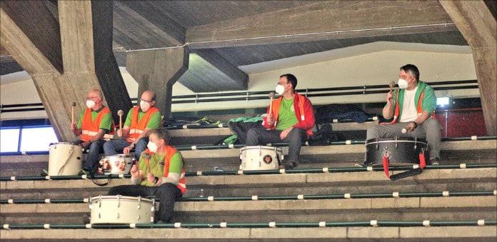 Menschen mit Trommeln auf Stadiontribüne