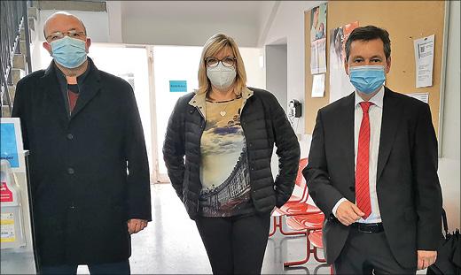 zwei Männer und eine Frau mit Mund-Nasen-Masken